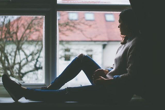 Frau alleine am Fenster